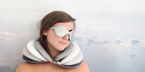 Girl wearing an eye mask and using travel pillow